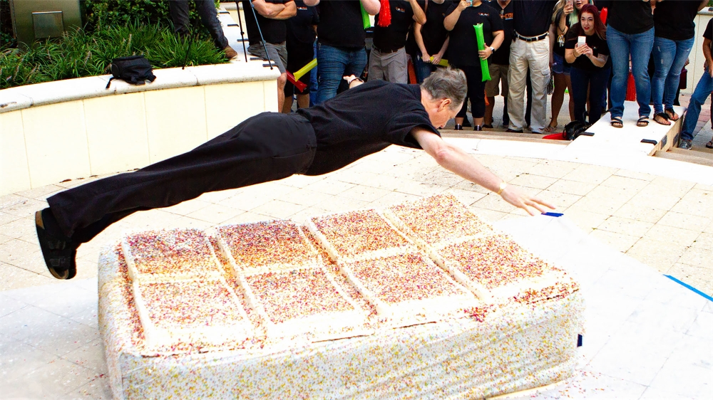 KnowBe4's CEO, Stu, jumps into a giant cake for KnowBe4's 8th anniversary