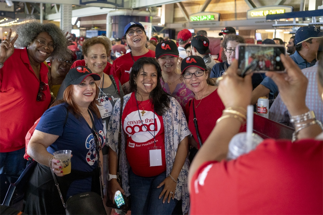 AARP CEO Jo Ann Jenkins poses with AARP staff during a Washington Nationals baseball game.