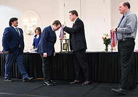 PAGE Executive Director awards medals at the Georgia Academic Decathlon.