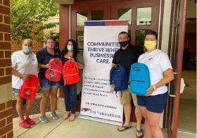 Several FNB employees hand out bookbags to children during a back-to-school supply drive.