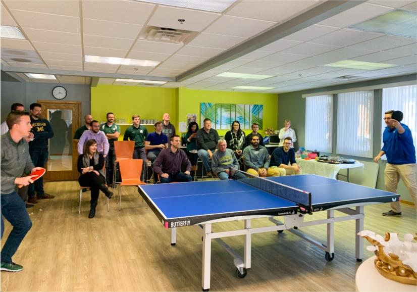 Employees watching a KL&A ping pong champion match.