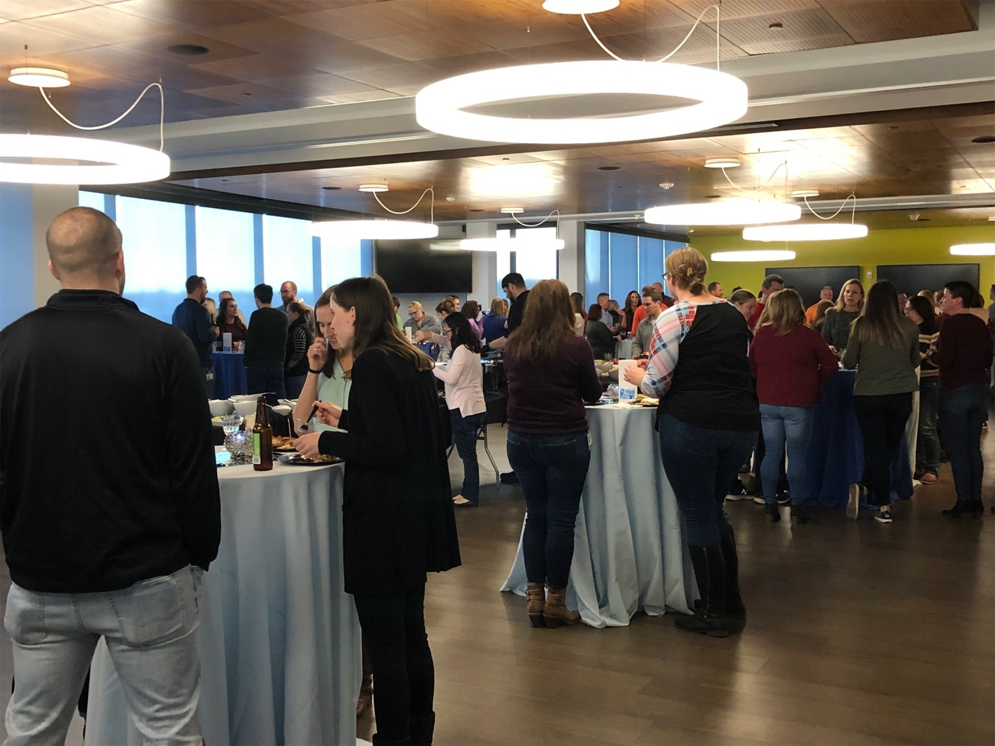 Associates gather to celebrate the holiday season in their brand new cafeteria that can be used as meeting space as well as for larger company sponsored events.