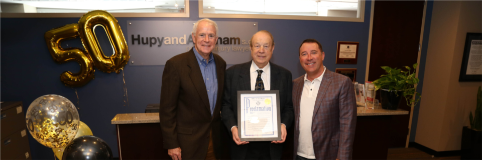 """Attorneys Michael Hupy and Jason Abraham with Milwaukee Mayor Tom Barrett and city proclamation declaring April 15, 2019 as """"Hupy and Abraham Day."""""""