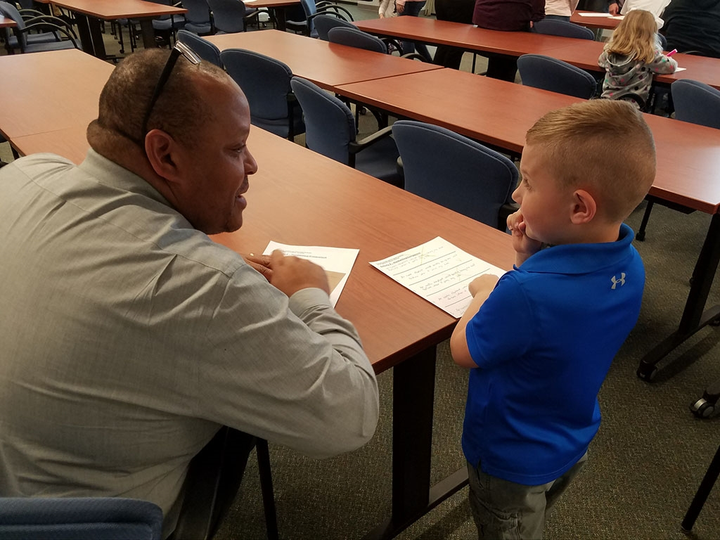 DCJS First Deputy Commissioner Mark White meets with a participant during the agency's 2019 Take Your Children to Work Day event.