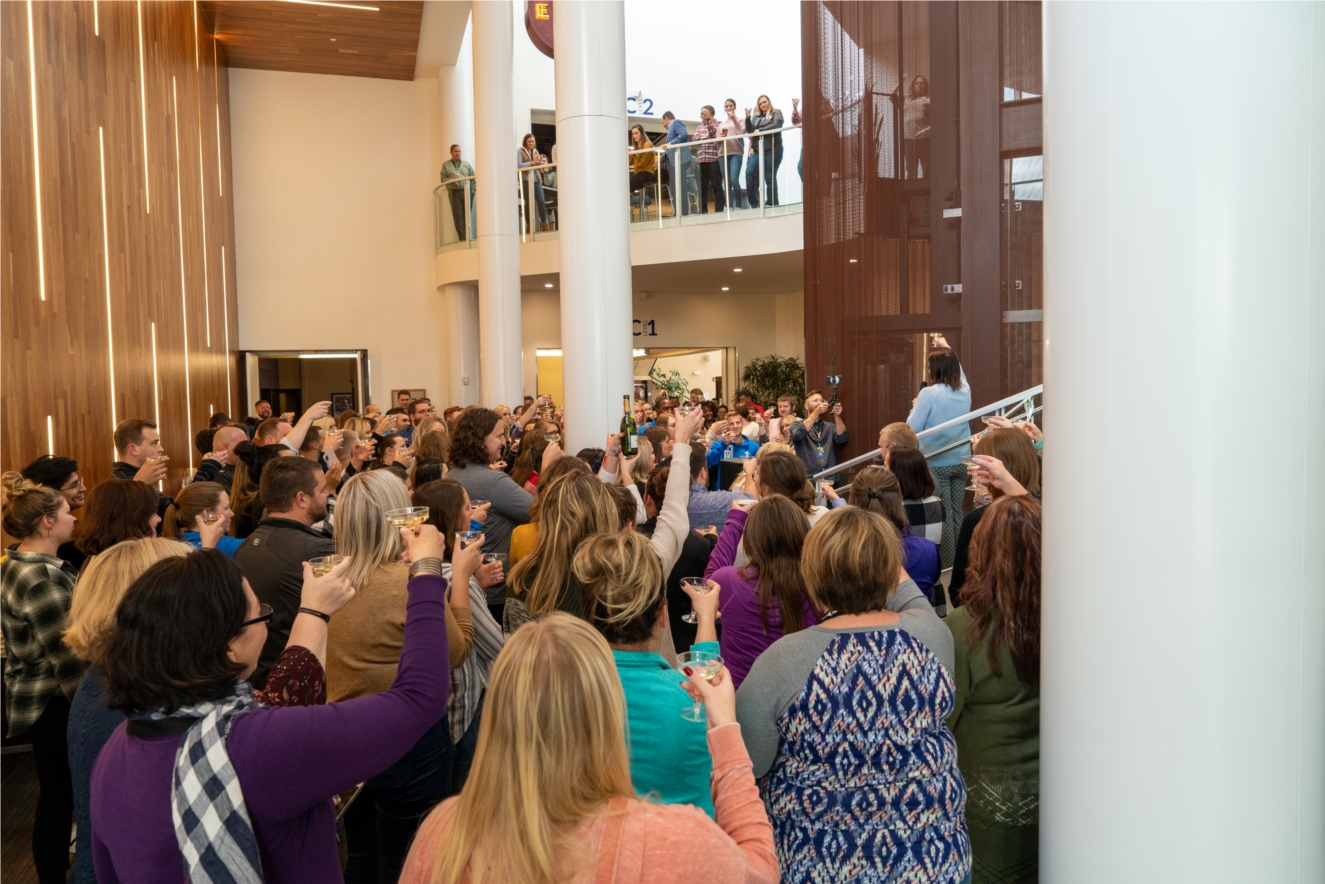 Employees gather for a company-wide champagne toast to celebrate VGM's #1 ranking in 2019. The event was broadcast via FaceBook Live to connect all of VGM's locations throughout the US.
