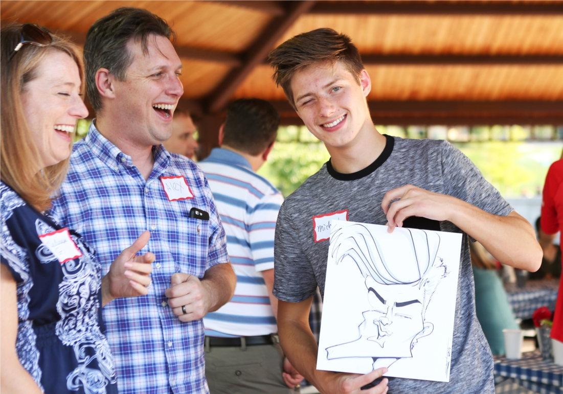 Son of an employee displays his characiture at the company picnic.