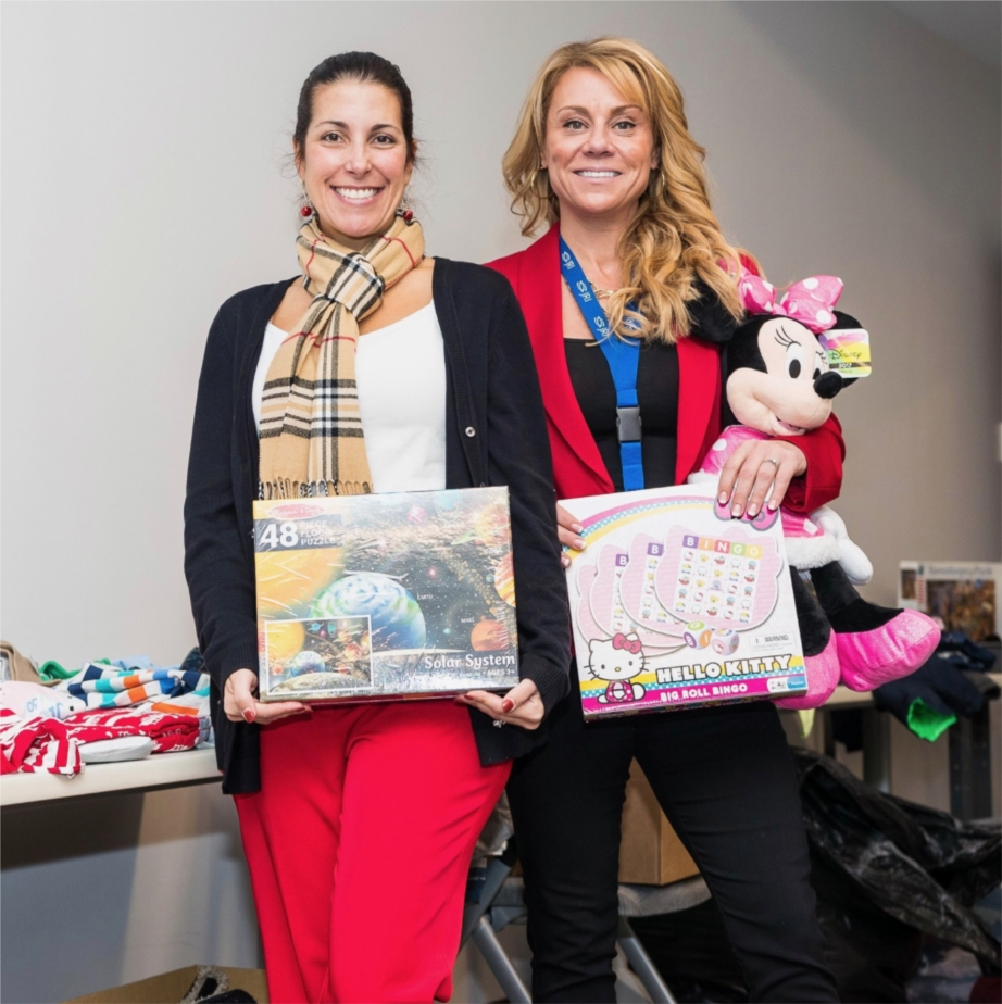Ann Schuler and Mia DeMarco show toys that were donated to those in need as part of JRI's Hope for All Season's program.