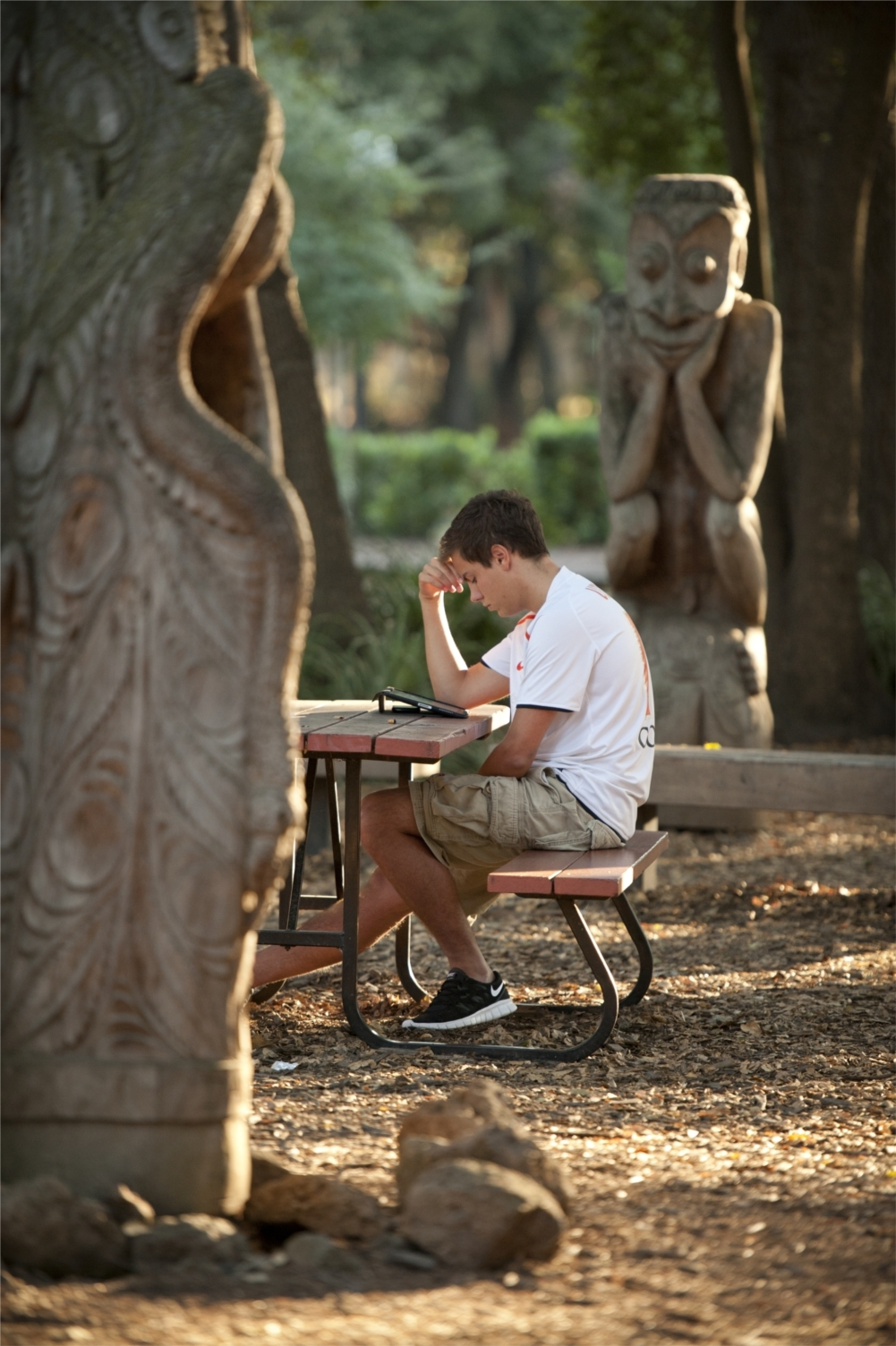 Stanford's campus offers unique settings for relaxation, or in this case, studying class notes in the Papua New Guinea art sculpture garden. Photo: Linda A. Cicero / Stanford News Service