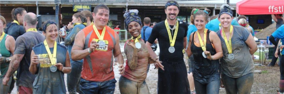 MTM employees celebrate completing an MTM-sponsored mud run.